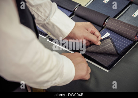 Tailor choosing fabric from swatch in tailors shop - Stock Photo