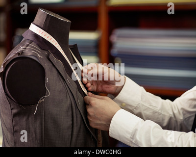Tailor measuring garment in traditional tailors shop - Stock Photo