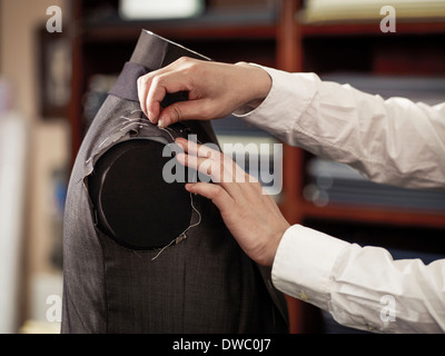 Tailor pinning garment in traditional tailors shop - Stock Photo