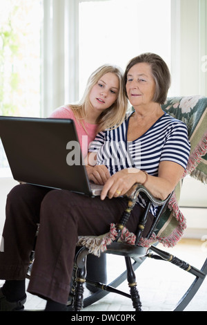 Grandmother and granddaughter using laptop at home - Stock Photo