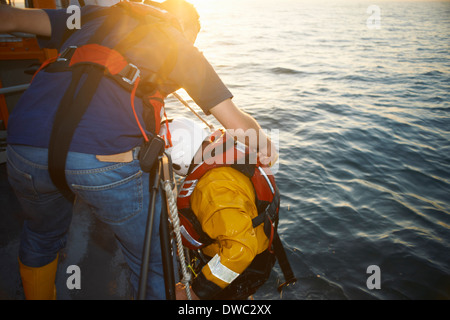 Lifeboat crew training and pulling up team member from sea - Stock Photo