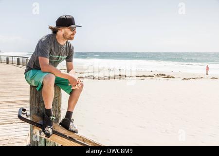 Young man sitting on wooden post, Laguna Beach, California, USA - Stock Photo