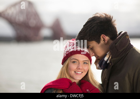 A young couple pose in front of the Forth Rail Bridge in Queensferry, near Edinburgh, Scotland - Stock Photo