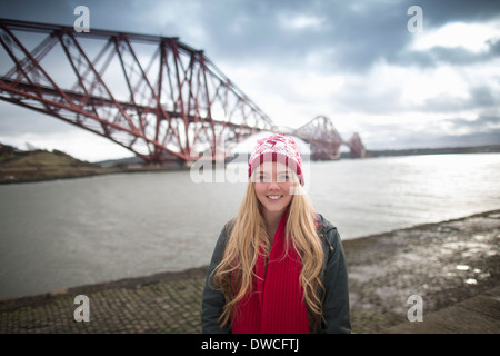 A young womans poses in front of the Forth Rail Bridge in Queensferry, near Edinburgh, Scotland - Stock Photo