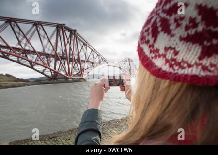 A young woman taking photograph of the Forth Rail Bridge in Queensferry, near Edinburgh, Scotland - Stock Photo