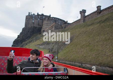 A young couple on an open-top bus tour of Edinburgh Scotland - Stock Photo