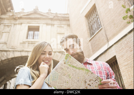 Young tourist couple looking at map outside Valencia Cathedral, Valencia, Spain - Stock Photo