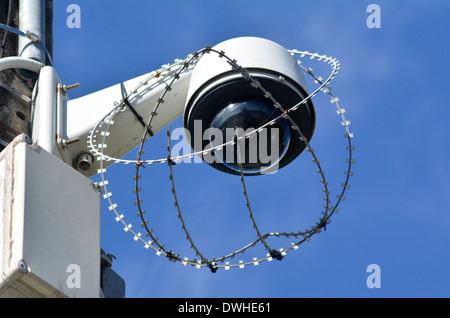 One security surveillance camera protected with barbed wire against vandalism and crime. concept photo of security. - Stock Photo