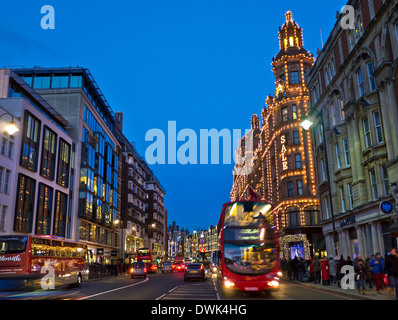 Brompton Road and Harrods department store at dusk with lit 'Sale' sign shoppers red buses and taxis Knightsbridge - Stock Photo