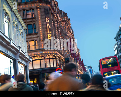 SALE SIGN CROWDS Harrods department store at dusk with lit 'Sale' sign and crowds of shoppers taxi and red bus Knightsbridge - Stock Photo