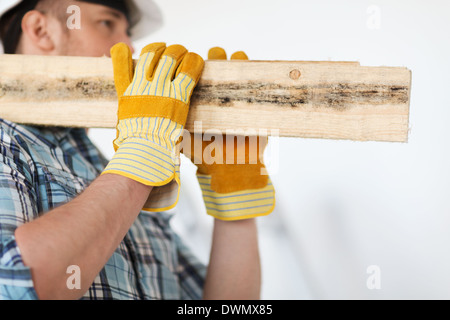 close up of male in gloves carrying wooden boards - Stock Photo
