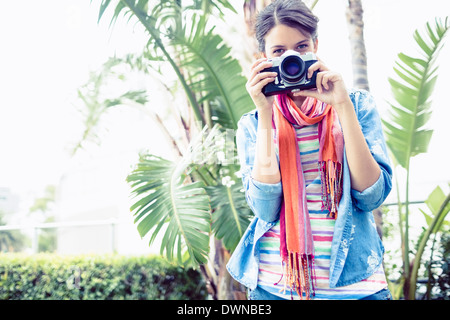 Brunette taking a photo outside smiling at camera - Stock Photo