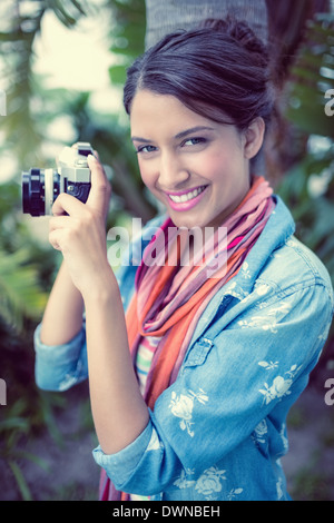 Cheerful brunette taking a photo outside smiling at camera - Stock Photo