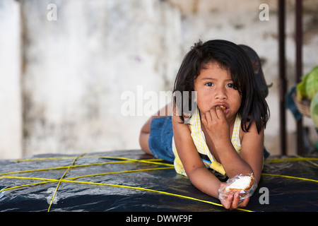 A young girl lies on a table in fruit stall in the market of the mountain town of Juayua on the rutas de la flores, - Stock Photo