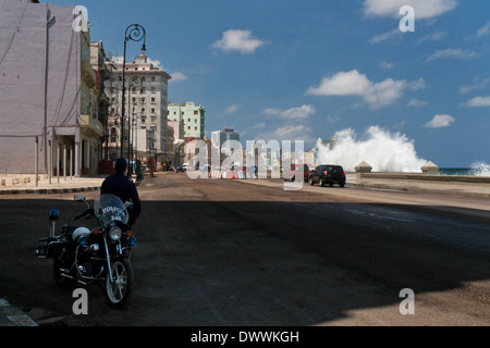 Policeman and his police bike watching traffic on the Malecón in La Habana Vieja, Havana, Cuba - Stock Photo