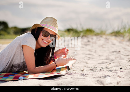 Portrait of happy woman holding mobile phone while lying on picnic blanket - Stock Photo