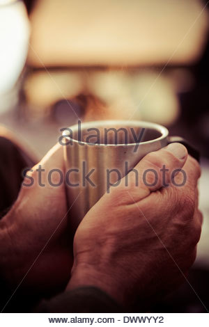 Man's hands holding coffee cup in tent - Stock Photo
