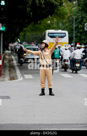 A traffic policeman directs traffic during the Hanoi rush-hour. Hanoi, Vietnam, Southeast Asia - Stock Photo