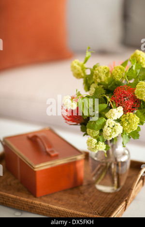 Spider mums and green and white viburnum flower bouquet in vase on tray with leather box - Stock Photo