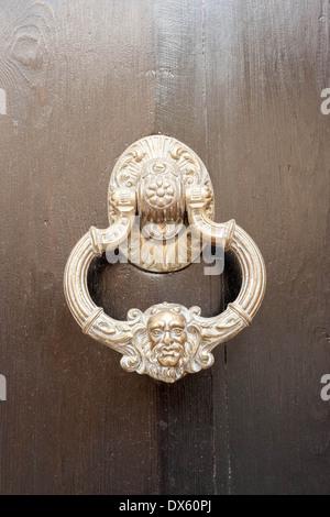 Face on a brass door knocker in Gaucin in Southern Spain. - Stock Photo