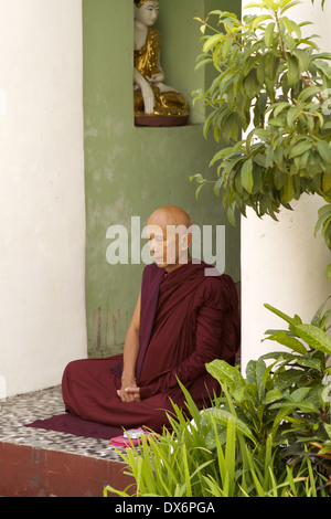 Burmese Monk identifiable by his dark red robes sits in contemplation in a side alcove of Shwedagon Pagoda complex - Stock Photo