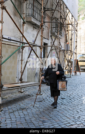 A women walks in alley in Alfama, Lisbon, Portugal. - Stock Photo
