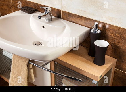 detail of a modern bathroom with sink and accessories, bathroom cabinet and brown bathroom tiles - Stock Photo