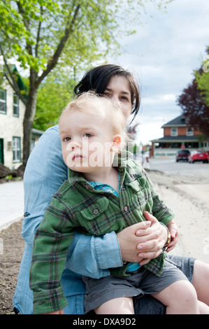 Toddler boy sitting on mother's lap outside on the curb - Stock Photo