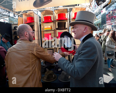 A hat seller selling top hats in Victorian Spitalfields Market near Brick Lane and Liverpool Street Station in East - Stock Photo