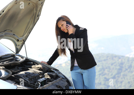 Woman on the phone looking her crash breakdown car in a road in the middle of the mountain - Stock Photo