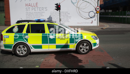 999 Emergency responder car _ NHS North West ambulance speeding through Ancoats in Manchester, UK - Stock Photo