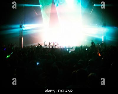 Fans facing illuminated stage - Stock Photo
