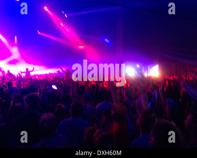 Crowd facing illuminated stage - Stock Photo