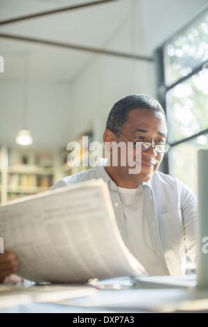 Senior man reading newspaper and using laptop - Stock Photo