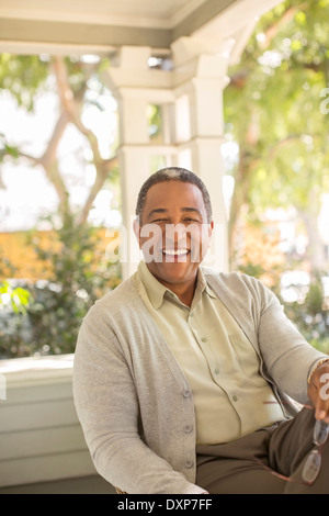 Portrait of laughing senior man on porch - Stock Photo