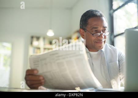 Senior man with newspaper using laptop - Stock Photo