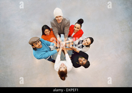 Group of happy young students showing. Top view of multiethnic group of young people putting their hands together. - Stock Photo