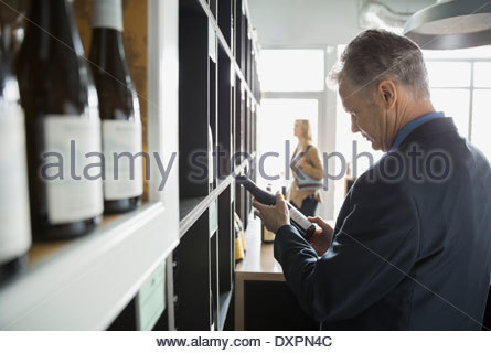 Man reading label on bottle in wine store - Stock Photo