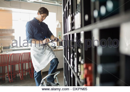 Sommelier taking inventory in wine store - Stock Photo