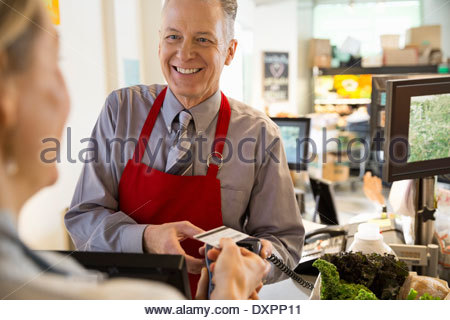 Woman paying clerk for groceries in market - Stock Photo