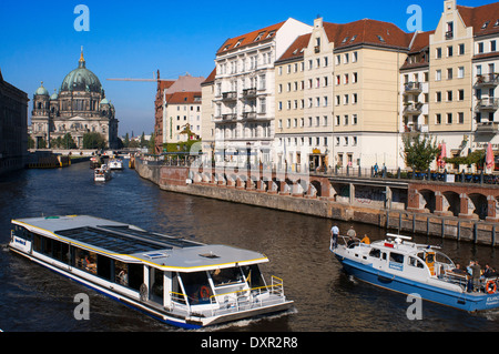 A tourist boat on the Spree river alongside The Nikolaiviertel or St. Nicholas Quarter on a sunny day. Nicholas - Stock Photo