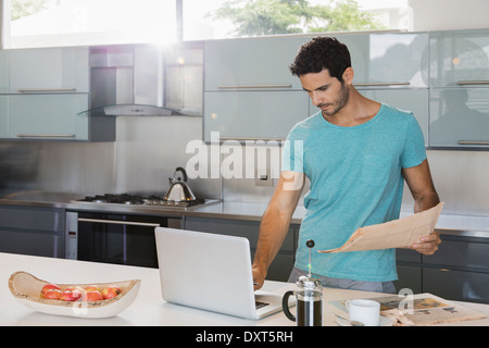 Man with newspaper using laptop in kitchen - Stock Photo