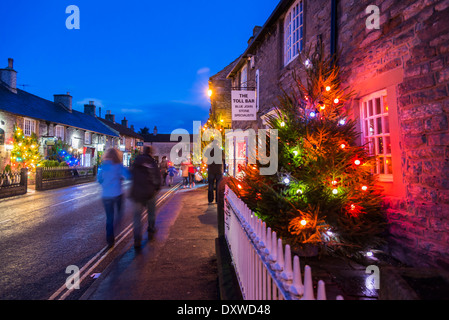 Christmas lights and trees illuminate the streets of Castleton in the Peak District Derbyshire - Stock Photo
