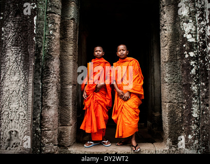 Two young monks pose for a portrait at the Bayon temple in Angkor Thom, Cambodia. - Stock Photo