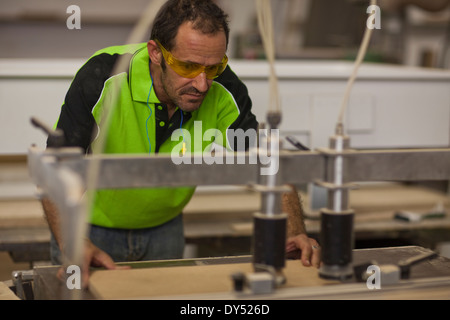 Carpenter cutting wood on table saw in workshop - Stock Photo