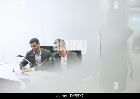 Male business colleagues using digital tablet in office - Stock Photo