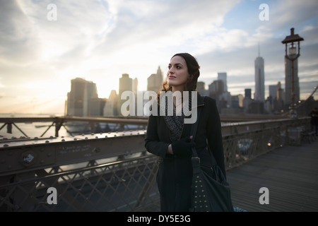 Young woman strolling on Brooklyn bridge, New York, USA - Stock Photo
