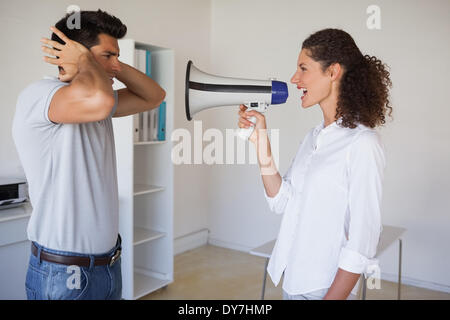 Casual businesswoman shouting at colleague through megaphone - Stock Photo