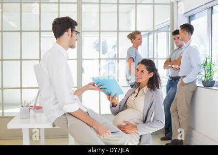 Pregnant businesswoman talking with colleague sitting at desk - Stock Photo