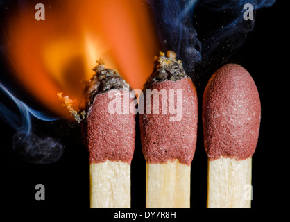 Matches being lit showing flames at the point of ignition, on a black background. Burning matches after being ignited. - Stock Photo